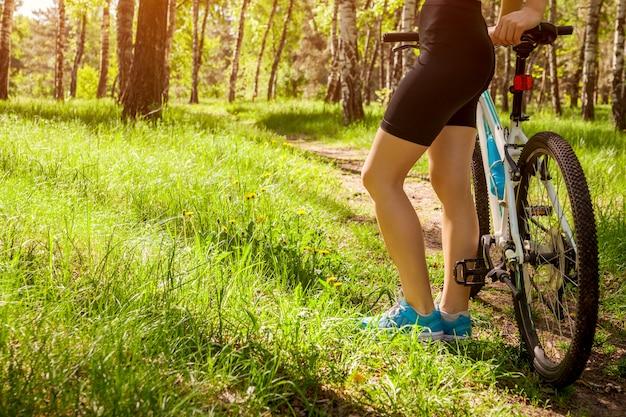 Młoda kobieta rowerzysta jedzie halnego bicykl w wiosna lesie.