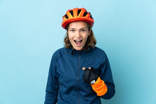 Młoda kobieta rowerzysta na białym tle na niebieskiej ścianie z niespodzianką wyraz twarzy