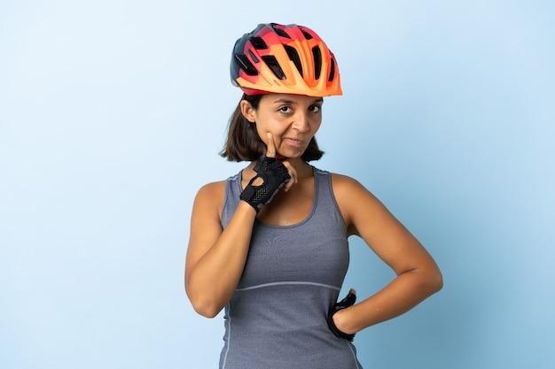 Młoda kobieta rowerzysta na białym tle na niebieskim tle i myślenia