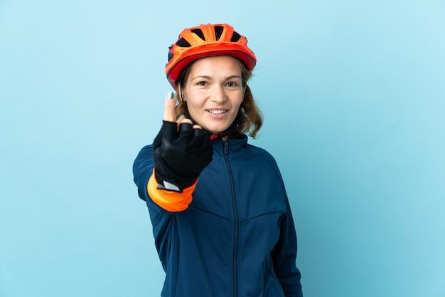 Młoda kobieta rowerzysta na białym tle na niebieskim tle robi nadchodzącym gestowi