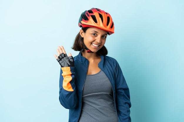 Młoda kobieta rowerzysta na białym tle na niebiesko salutowanie ręką z happy wypowiedzi