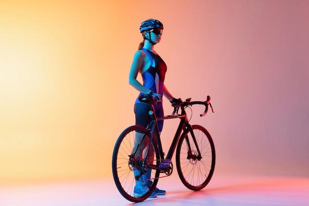 Młoda kobieta rowerzysta na rowerze na białym tle na ścianie gradientowej