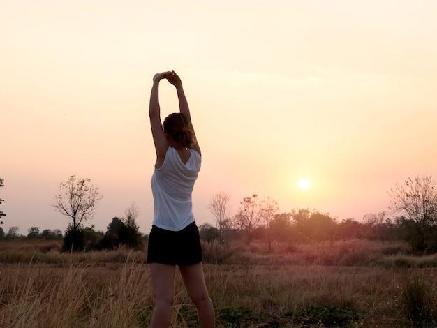 Młoda kobieta, rozciągając ramiona na piękny jasny zachód słońca niebo w pobliżu pola lato z miejsca na kopię