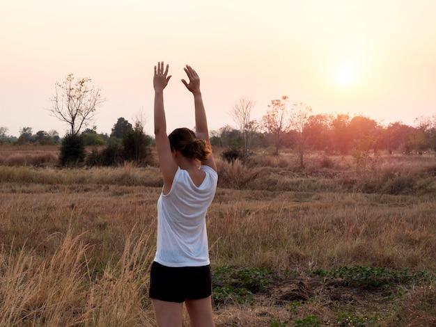Młoda kobieta, rozciągając ramiona na piękny jasny zachód słońca niebo w pobliżu pola letniego