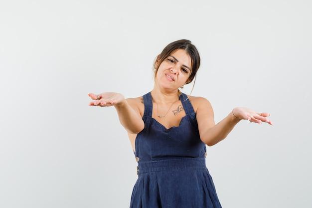 Młoda kobieta, rozciągając ręce, oferując coś w sukience i wyglądając ponętnie