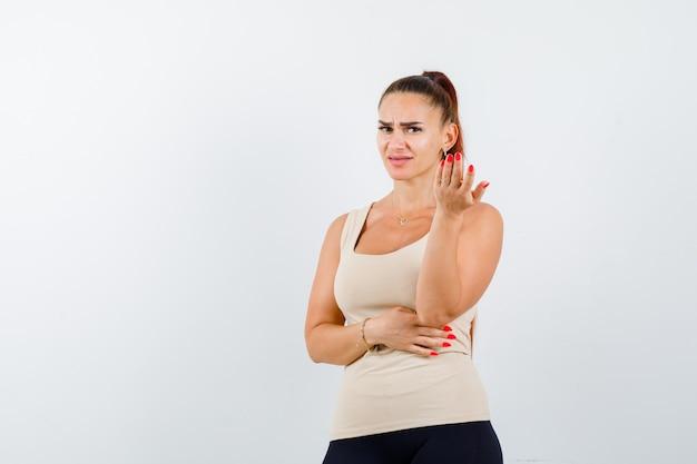 Młoda kobieta rozciągająca rękę w pytającym geście w beżowym podkoszulku bez rękawów i patrząc niezdecydowany. przedni widok.