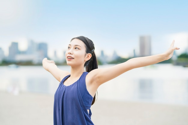 Młoda kobieta rozciągająca się i biorąc głęboki oddech na plaży miasta