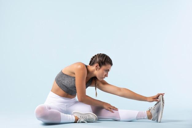 Młoda kobieta rozciągająca się przed treningiem