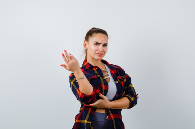 Młoda kobieta rozciągania ręki w przesłuchaniu gest w top, kraciaste koszule i patrząc poważnie, widok z przodu.