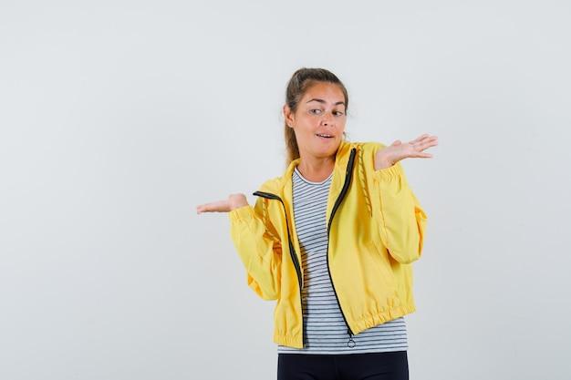 Młoda kobieta rozkłada dłonie na bok w koszulce, kurtce i wygląda pięknie. przedni widok.