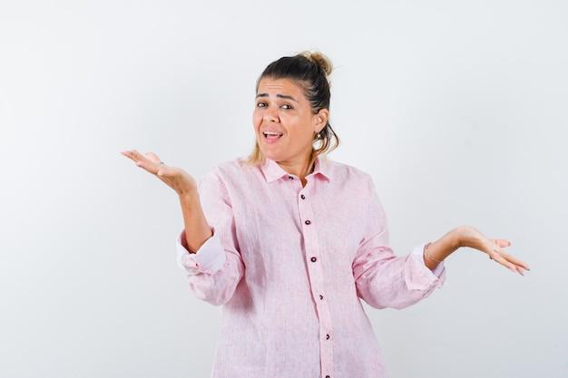 Młoda kobieta rozkłada dłonie w różowej koszuli i wygląda na szczęśliwą