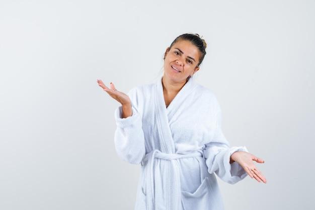 Młoda kobieta rozkłada dłonie w szlafroku i wygląda na szczęśliwą