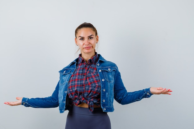 Młoda kobieta rozkładając dłonie na bok w kraciastej koszuli, kurtce, spodniach i patrząc niezdecydowany, widok z przodu.