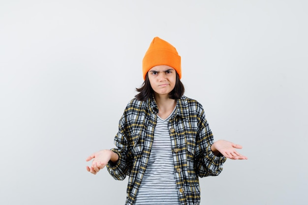 Młoda kobieta rozkładająca dłonie w pomarańczowym kapeluszu i kraciastej koszuli i wyglądająca ponuro