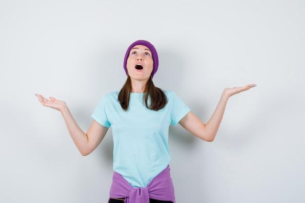Młoda kobieta rozkładająca ręce w pytający sposób, trzymająca szeroko otwarte usta w niebieskiej koszulce, fioletowej czapce i wyglądająca na zszokowaną, widok z przodu.