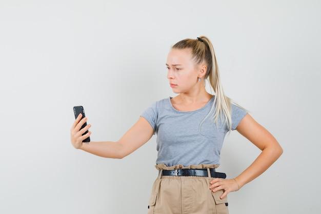 Młoda kobieta rozmawia na czacie wideo w t-shirt, spodnie i wygląda poważnie. przedni widok.