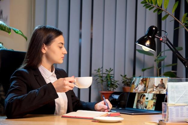 Młoda kobieta rozmawia podczas wideokonferencji z kolegami współpracownikami w domu
