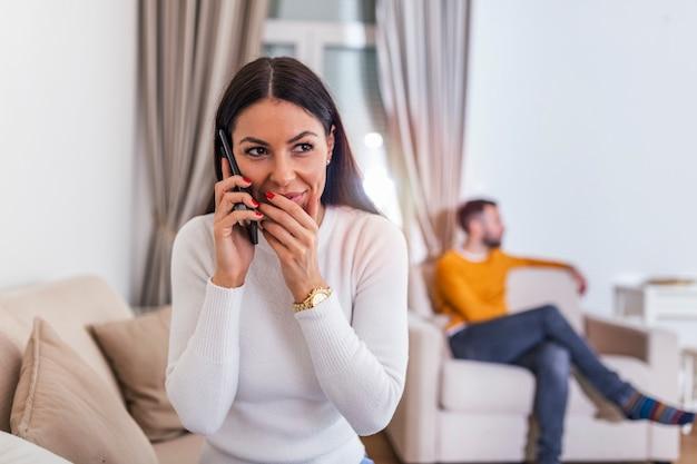Młoda kobieta rozmawia prywatnie przez telefon komórkowy, podczas gdy jej mąż ogląda telewizję z tyłu.