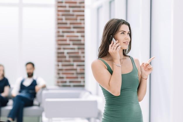 Młoda kobieta rozmawia przez smartfon stojący w biurze.zdjęcie z miejscem na kopię