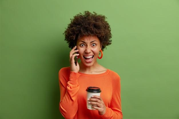 Młoda kobieta rozmawia przez smartfona napoje zabierają kawę złość podczas rozmowy wykrzykuje oburzona nosi sweter z długimi rękawami odizolowany na zielonej ścianie