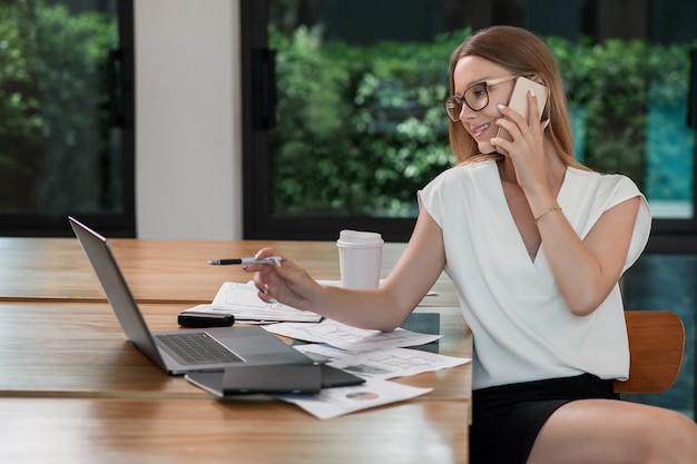Młoda kobieta rozmawia przez telefon i pracuje na laptopie
