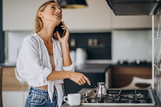 Młoda kobieta rozmawia przez telefon i robi poranną kawę