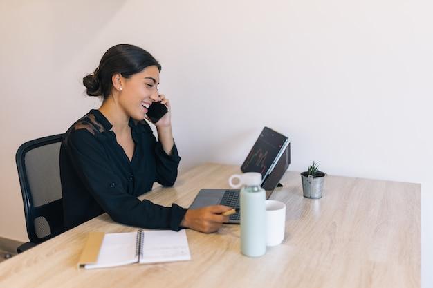 Młoda kobieta rozmawia przez telefon i śmieje się podczas inwestowania w kryptowaluty