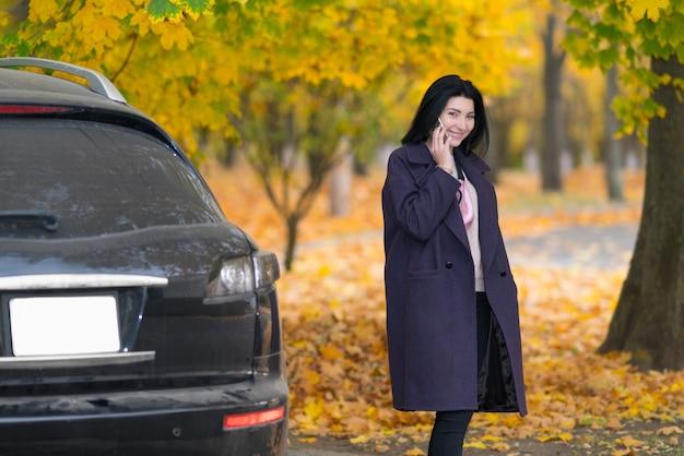 Młoda kobieta rozmawia przez telefon komórkowy, gdy wychodzi z samochodu w kolorowym jesiennym parku z drzewami