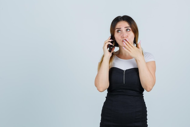 Młoda kobieta rozmawia przez telefon komórkowy, trzymając rękę nad ustami