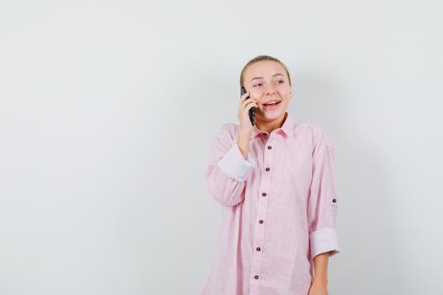 Młoda kobieta rozmawia przez telefon komórkowy w różowej koszuli i patrząc wesoło