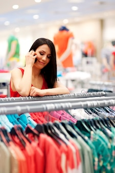 Młoda kobieta rozmawia przez telefon komórkowy w sklepie