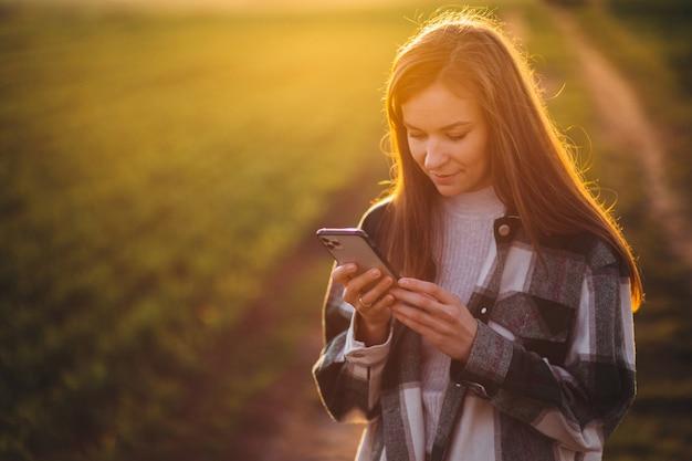Młoda kobieta rozmawia przez telefon na zachód słońca