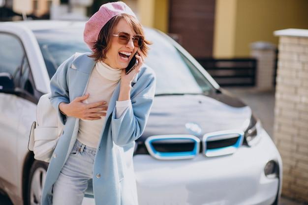 Młoda kobieta rozmawia przez telefon przez jej samochód elektryczny