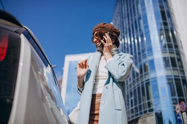 Młoda kobieta rozmawia przez telefon samochodem elektrycznym w centrum