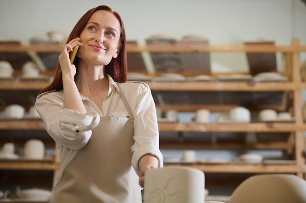 Młoda kobieta rozmawia przez telefon stojąc w warsztacie garncarskim