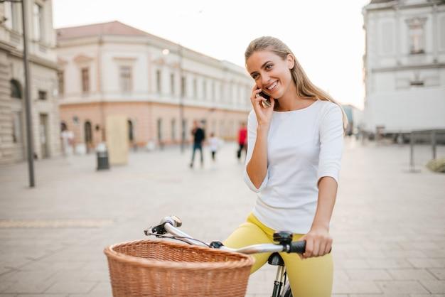 Młoda kobieta rozmawia przez telefon w mieście z rowerem.
