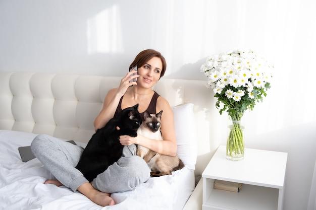 Młoda kobieta rozmawia przez telefon z dwoma kotami w białej sypialni z kwiatami.
