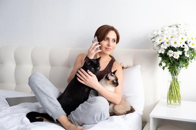 Młoda kobieta rozmawia przez telefon ze swoimi dwoma kotami w białej sypialni z kwiatami.