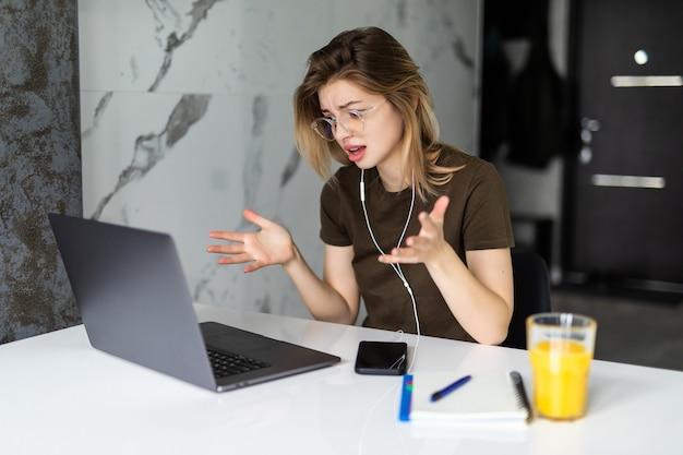 Młoda kobieta rozmawia przez wideorozmowę i macha ręką siedząc przy stole w kuchni