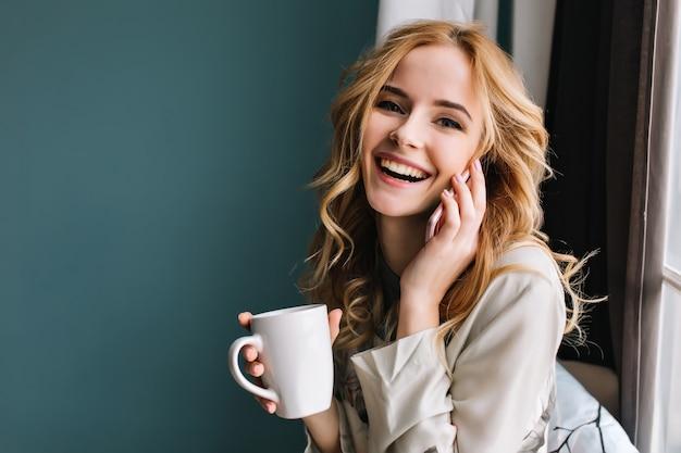 Młoda kobieta rozmawia telefon i śmieje się z filiżanką kawy, herbatą w ręku, szczęśliwy poranek. ma piękne, falowane blond włosy. pokój z niebieską, turkusową ścianą. ubrana w ładną koronkową piżamę.
