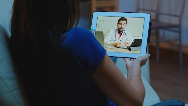 Młoda kobieta rozmawia z lekarzem przez kamerę internetową za pomocą tabletu