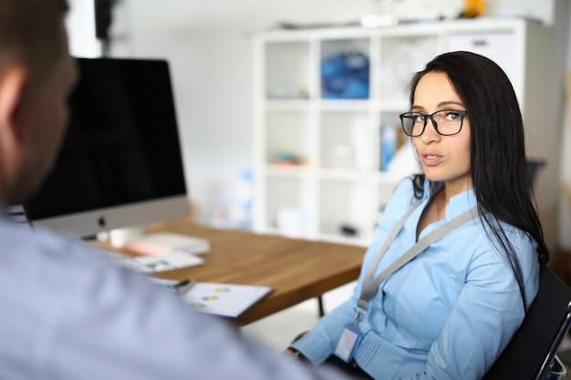 Młoda kobieta rozmawia z mężczyzną w miejscu pracy