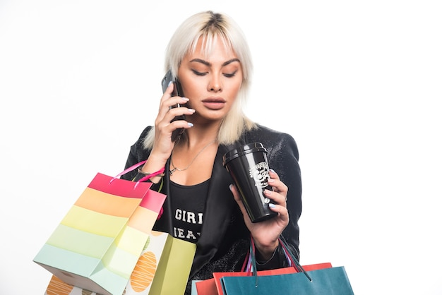 Młoda kobieta rozmawia z telefonem, trzymając torby na zakupy i kubek na białym tle. wysokiej jakości zdjęcie