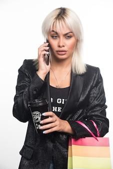 Młoda kobieta rozmawia z telefonem, trzymając worek i kubek na prezent. wysokiej jakości zdjęcie