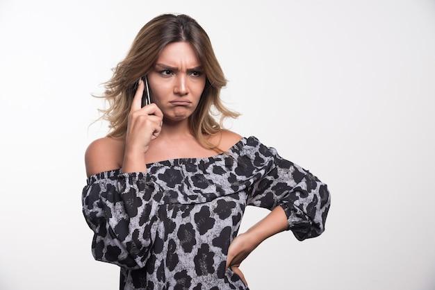Młoda kobieta rozmawia z telefonem z gniewnym wyrazem.