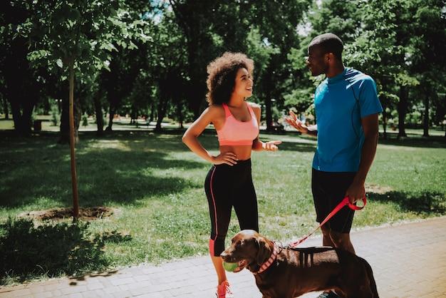Młoda kobieta rozmawia ze sportowym mężczyzną.