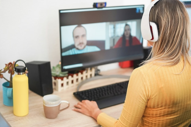 Młoda kobieta rozmawia ze swoimi kolegami w wideokonferencji w domu - skup się na słuchawkach