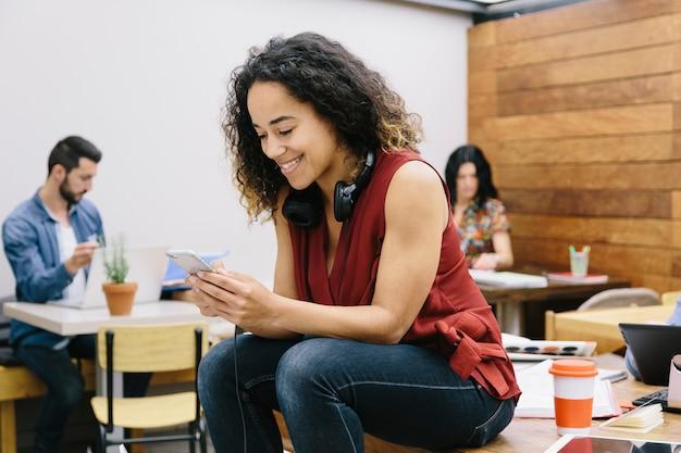 Młoda kobieta rozmawiająca ze swoim smartfonem w coworkingowej espace
