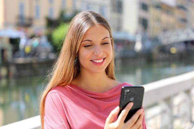 Młoda kobieta rozmowy wideo z aplikacji na smartfona na ulicy miasta