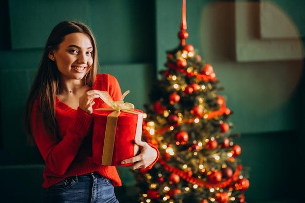Młoda kobieta rozpakowywania prezentu przez choinkę